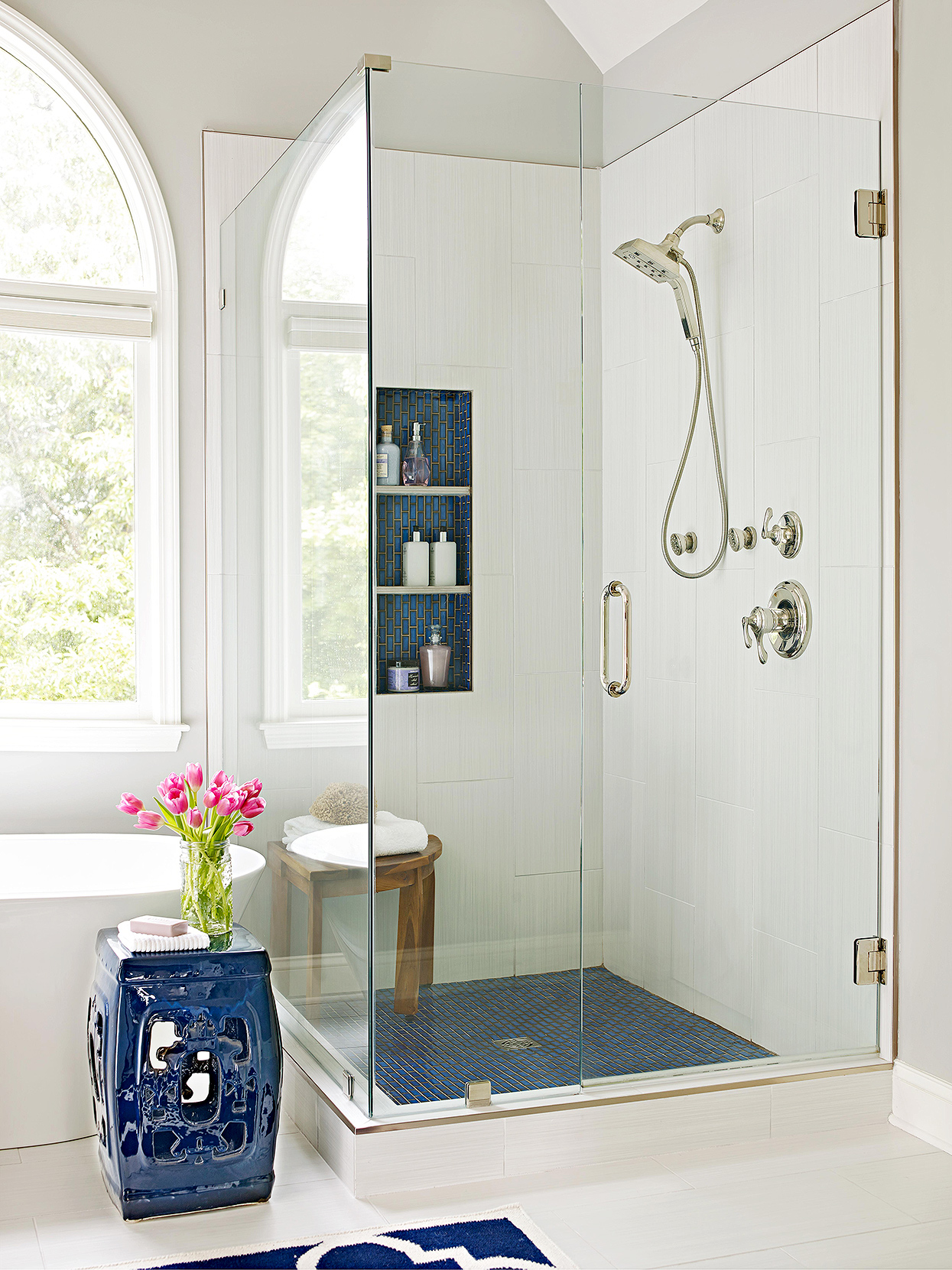 corner shower with glass doors and blue accent tile