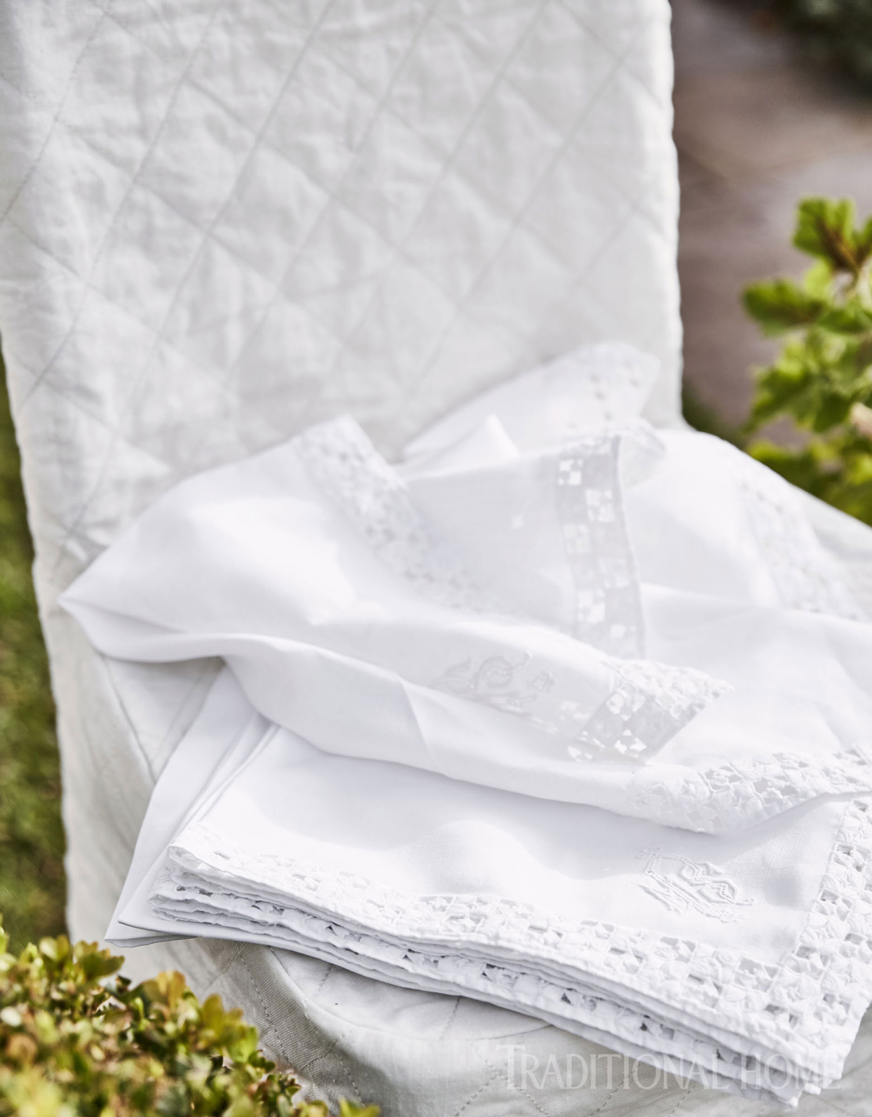 Vintage linens are numerous in Suzanne's inventory of entertaining wares; quilted slipcovers were fabricated using old linen army sheets from the Marché aux Puces de Saint-Ouen, Paris' renowned flea market.