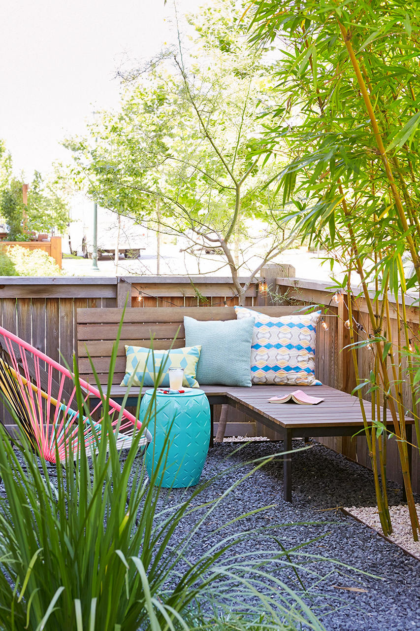 corner bench with pillows, blue table, lounger patio area