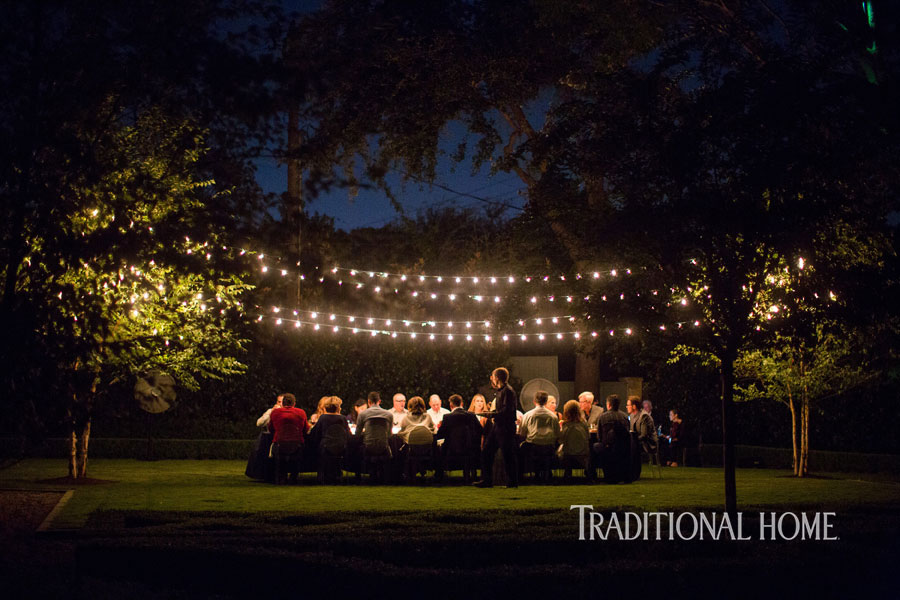 night shot guests at outdoor dinner table below lights