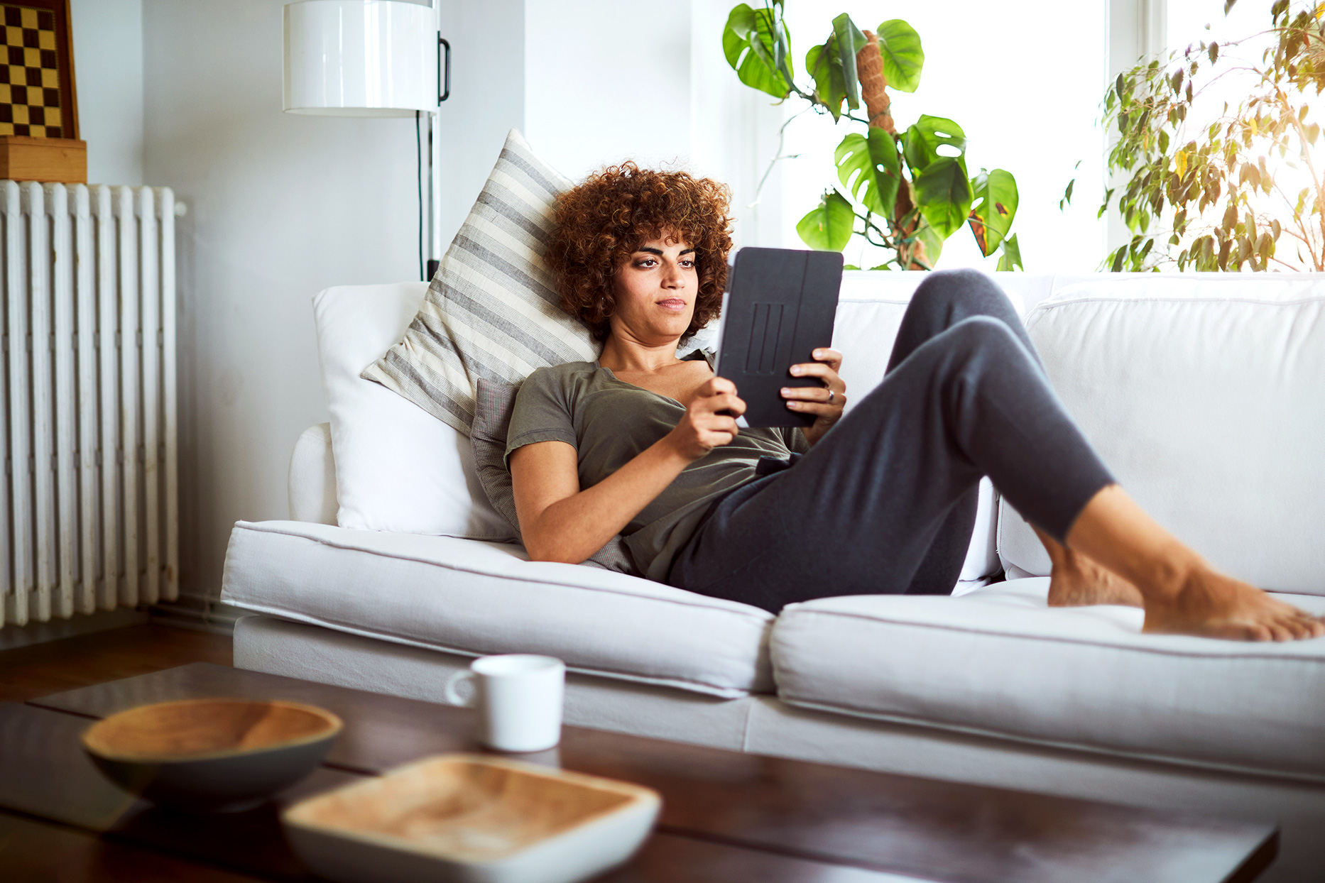 woman using ereader on couch