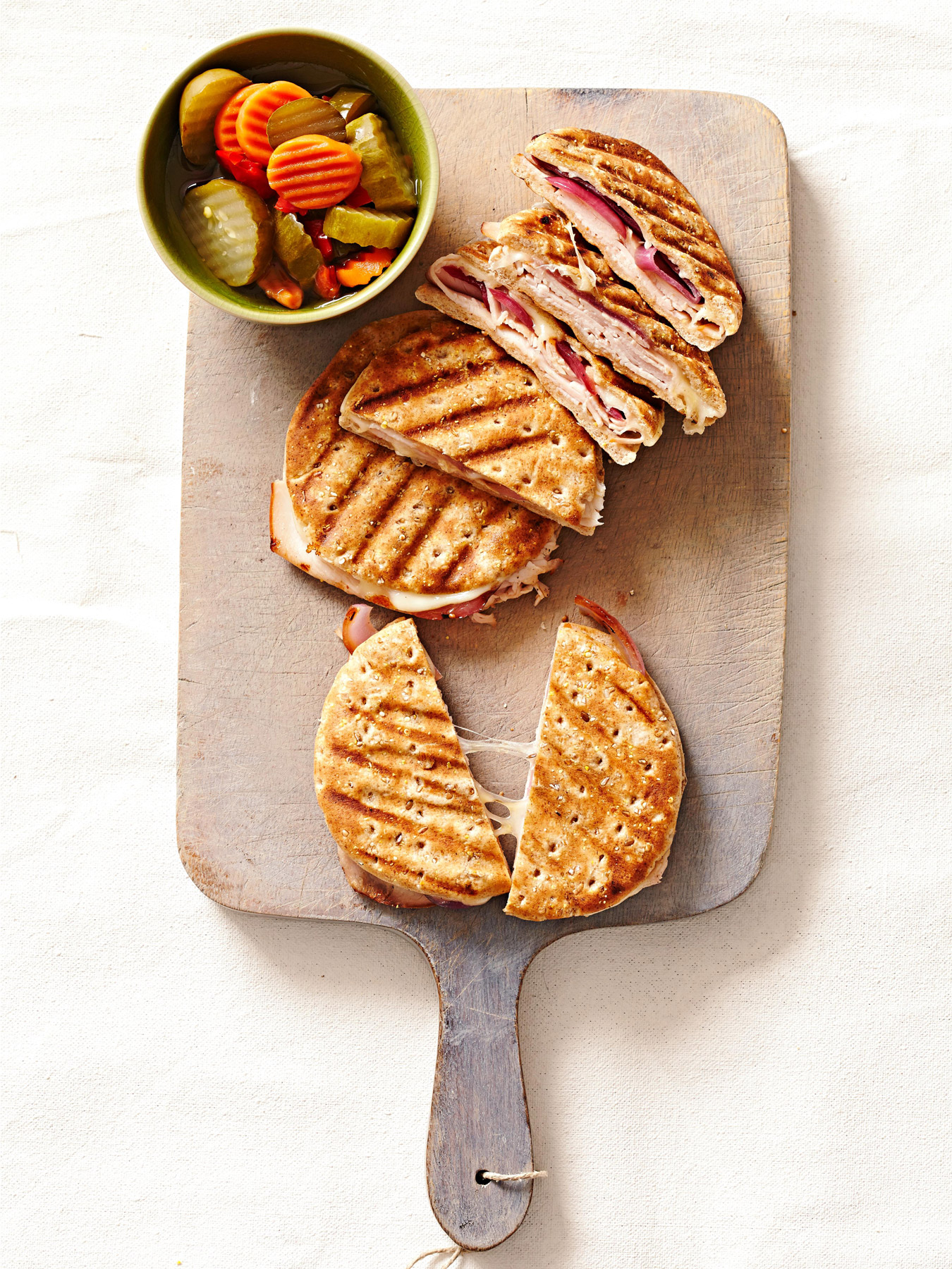 smoked turkey and grilled onion panini on cutting board