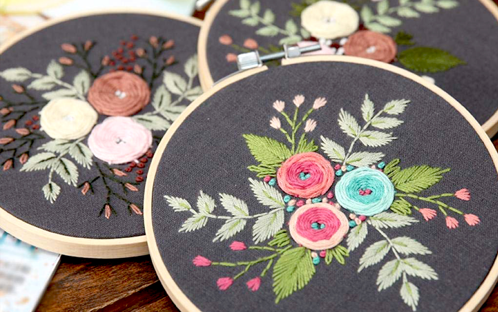 three floral embroidery hoops on a wooden table
