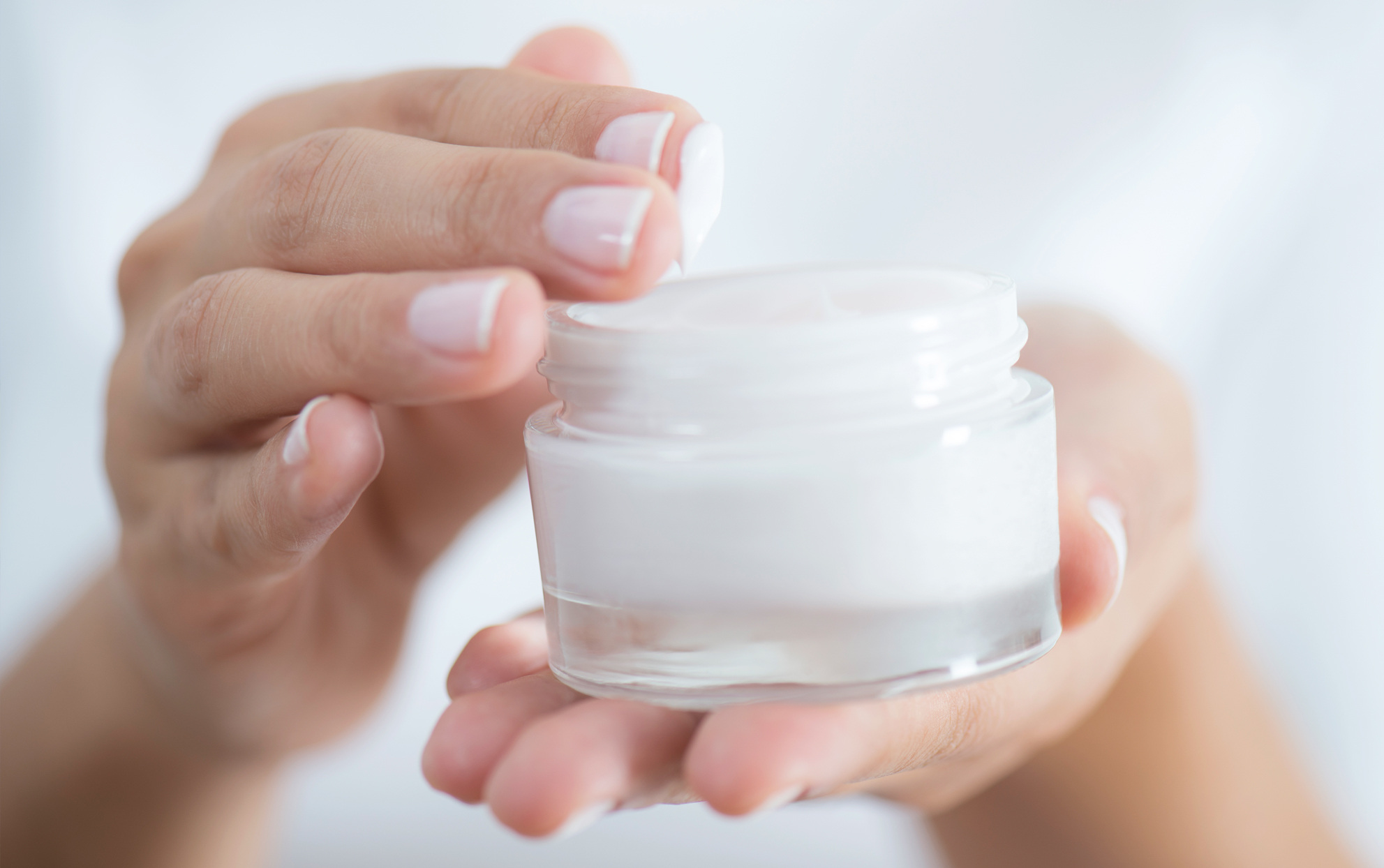 Woman using hand cream from a jar