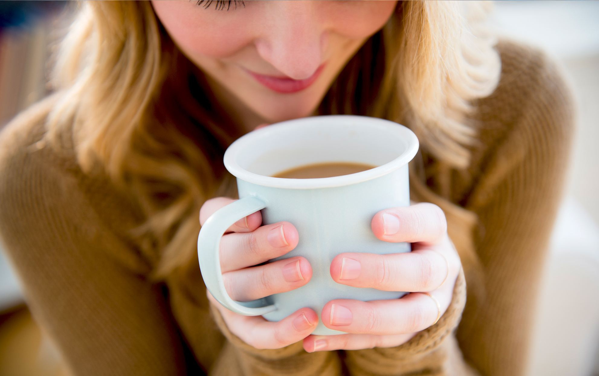 close up of woman holding a coffee mug wearing a brown sweater