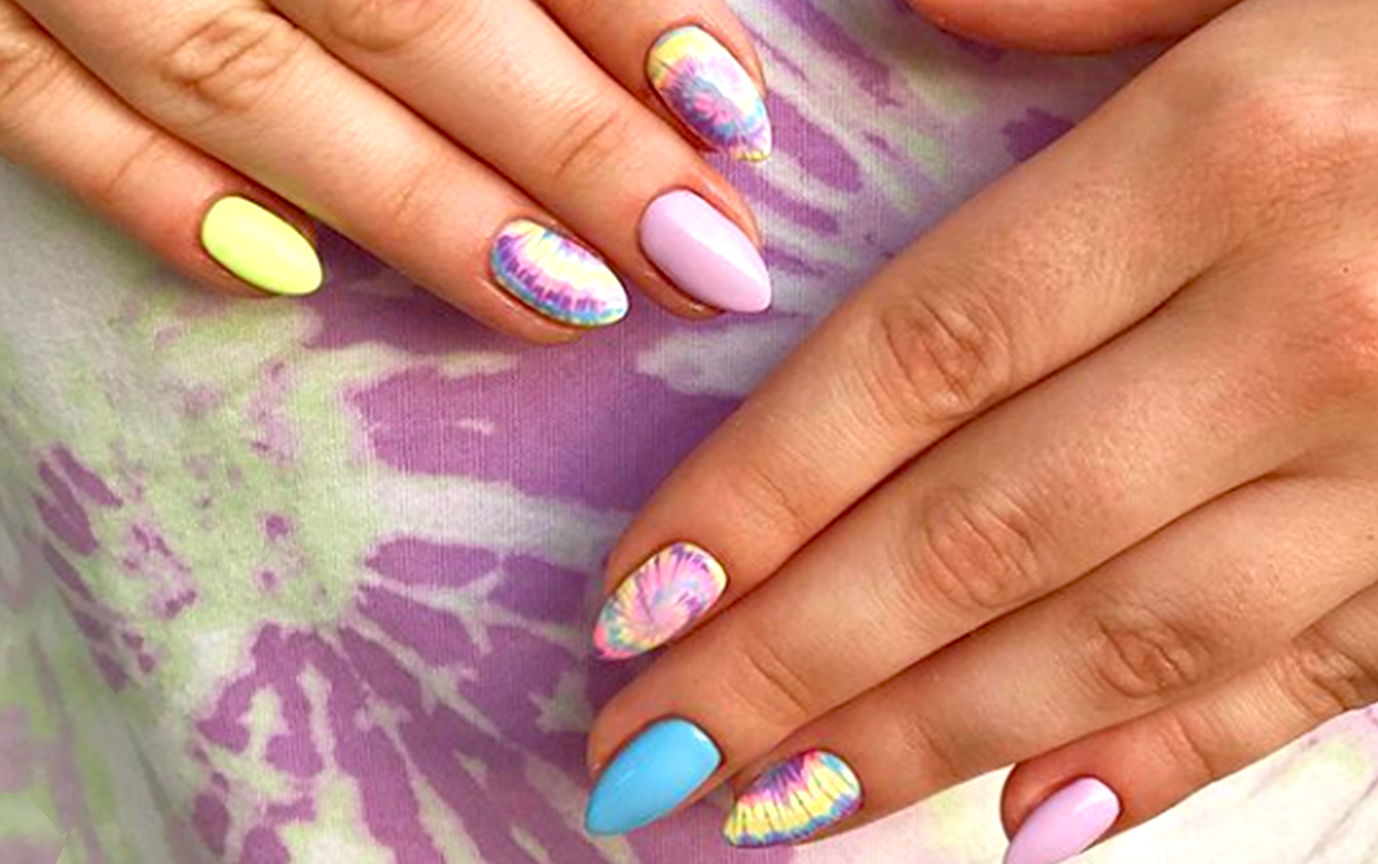 close up of a hand with tie dye nails on a tie dye fabric