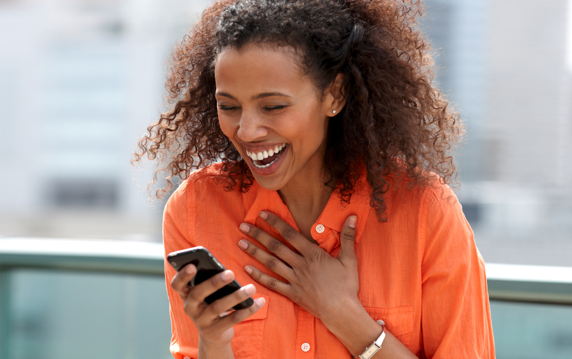 African American woman looking at her cell phone laughing outside