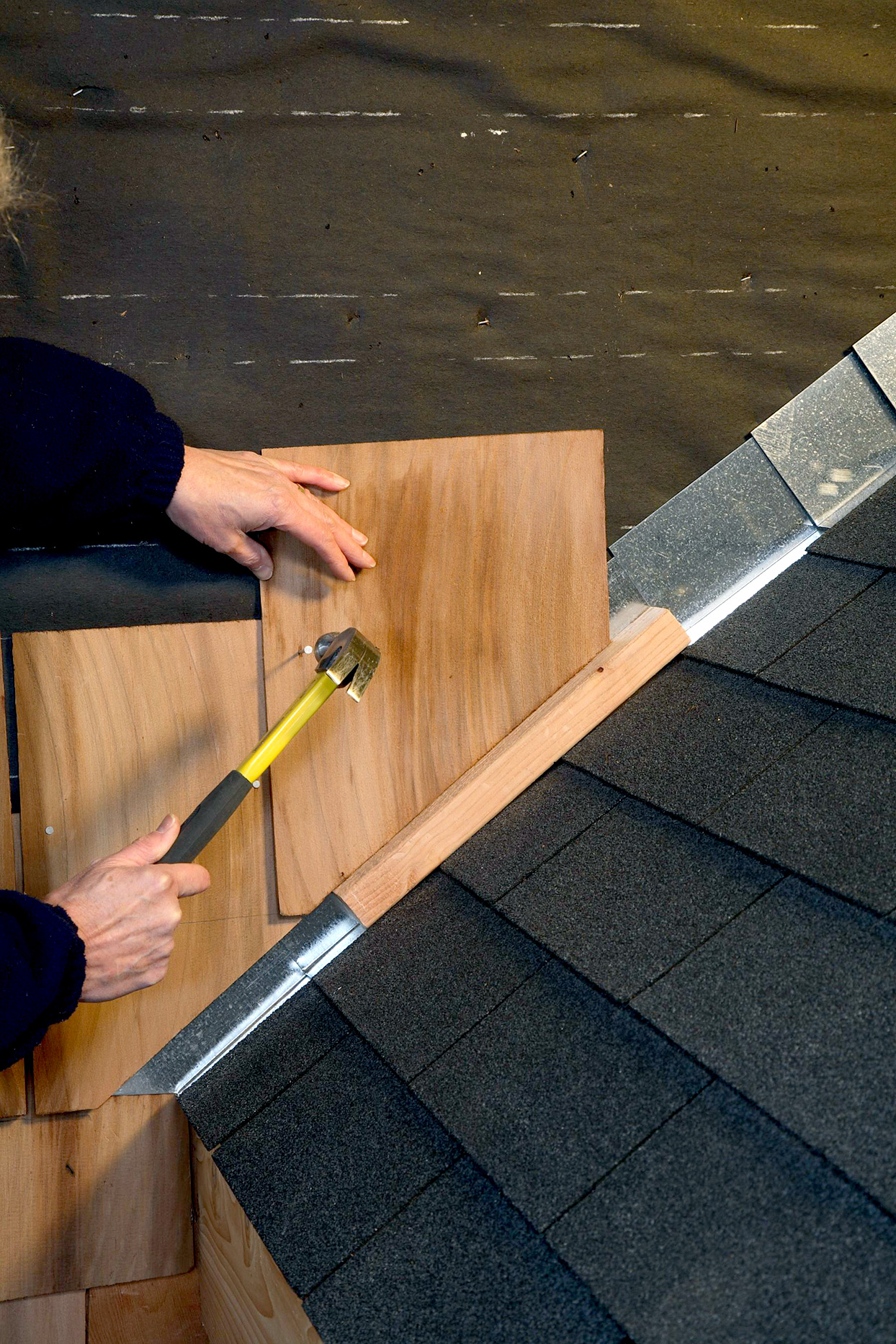 Attaching angle cut shingle along roofline, flashing installed beneath it