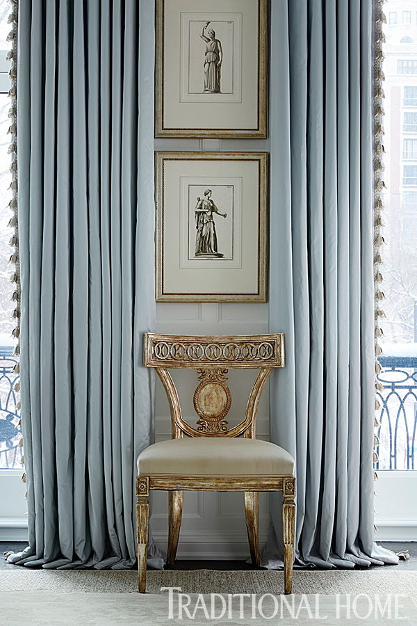 antique gold chair in front of long blue curtains