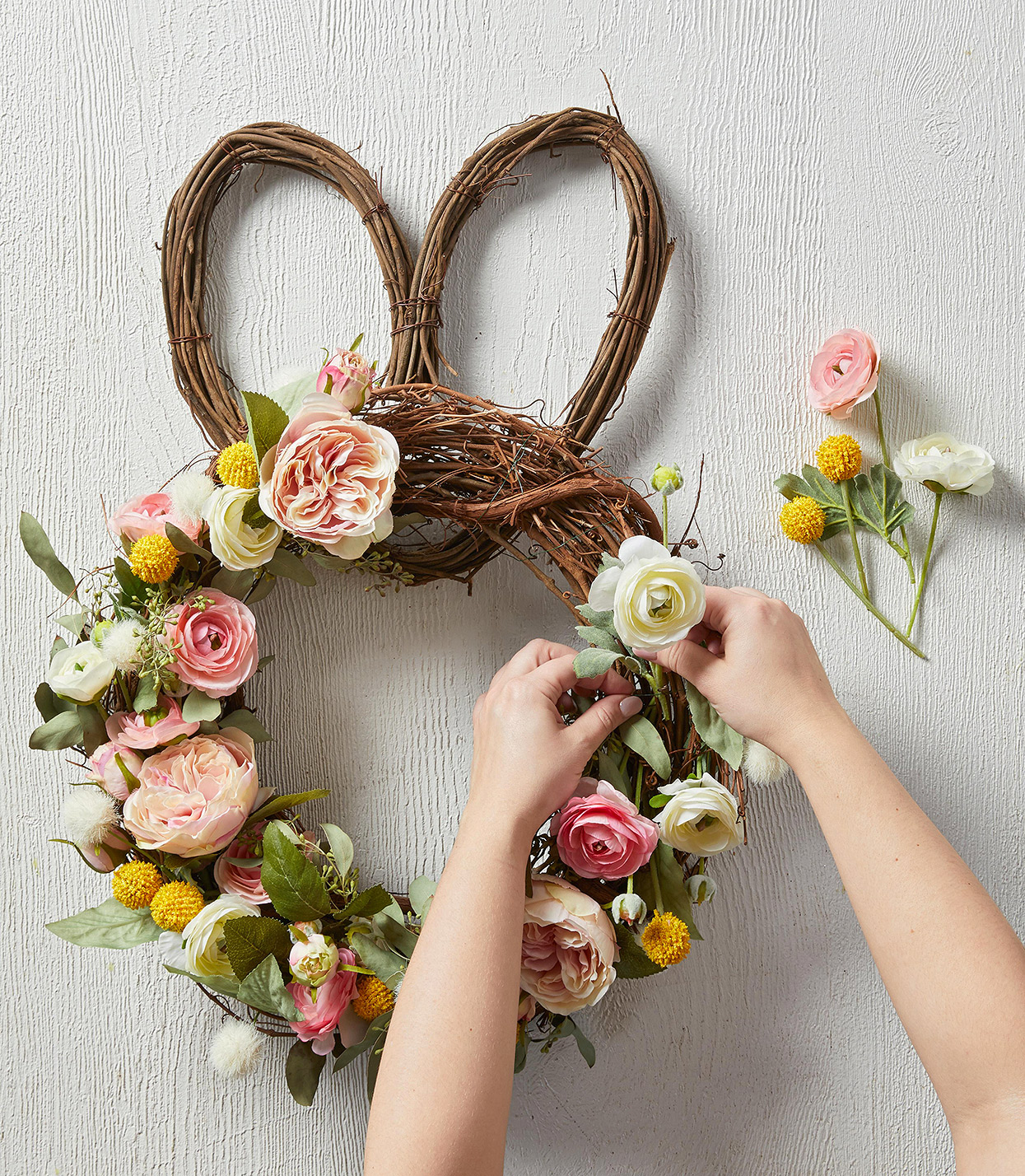woman placing artificial blooms on easter-shaped wreath