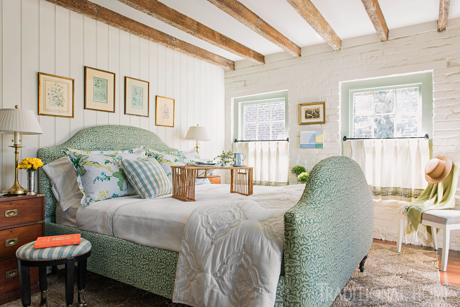 guest suite with exposed beams and green upholstered bed