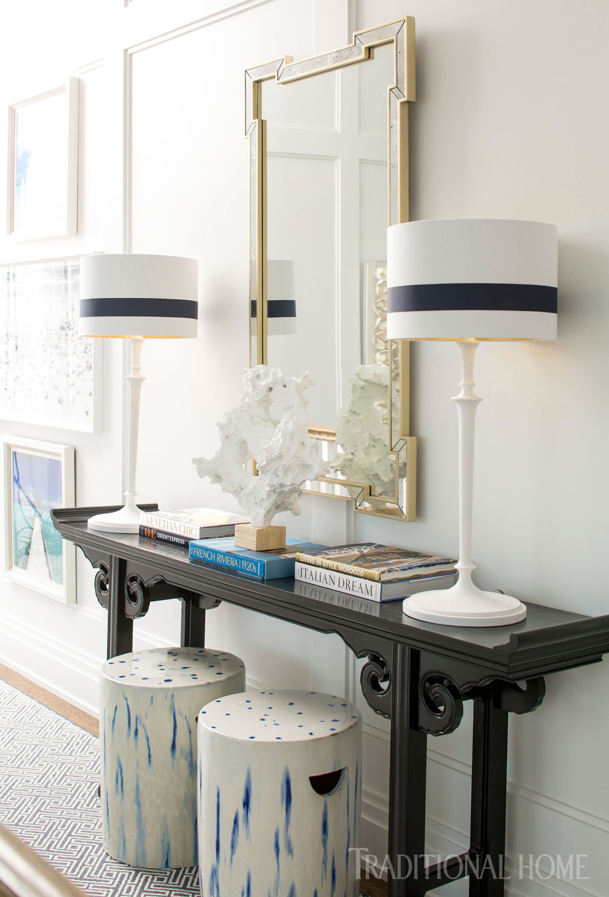 black console table with gold mirror and lamps