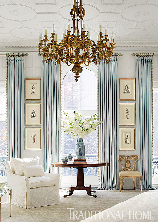 blue and white living room with large chandelier