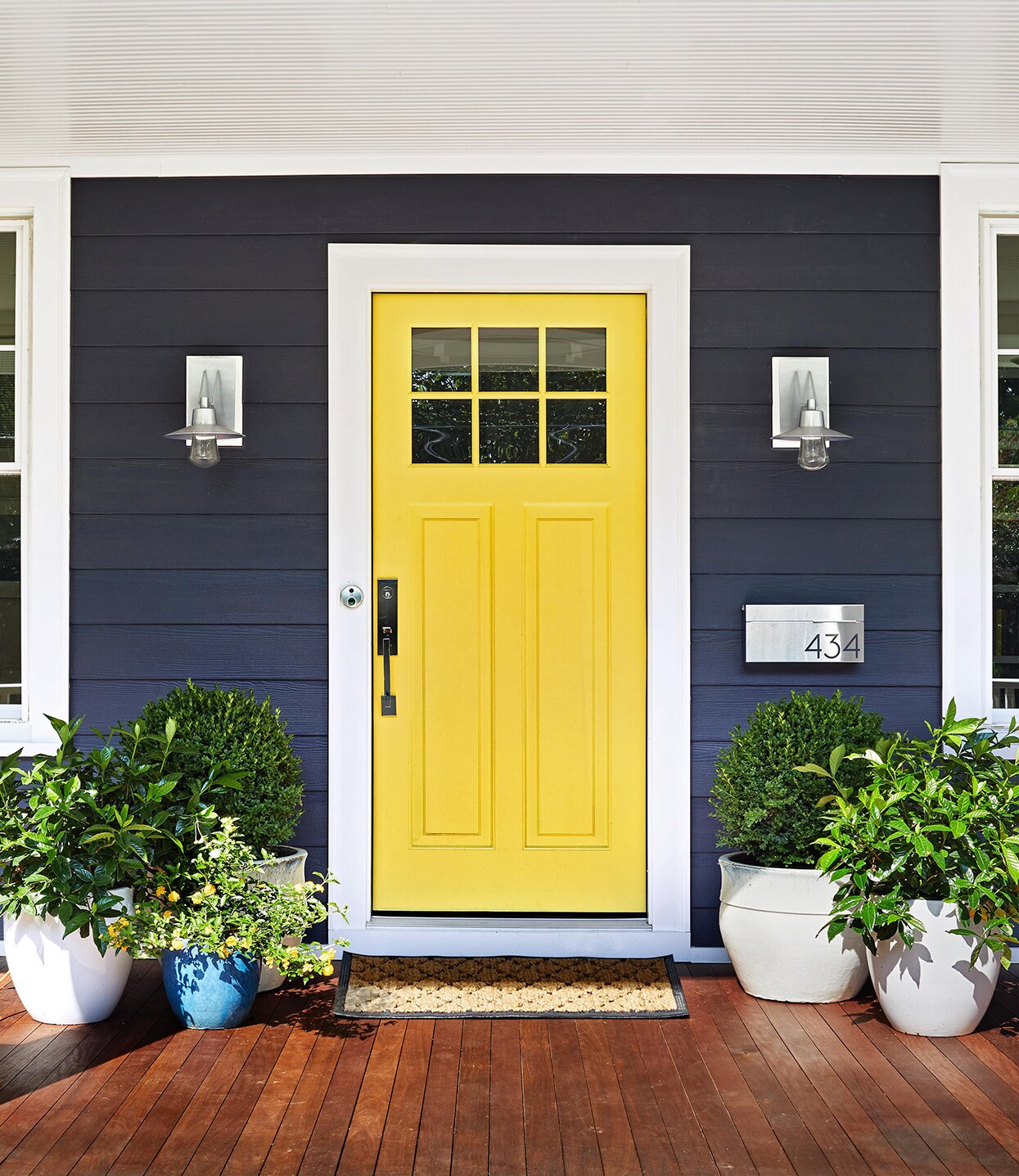 bright yellow front door on house with blue siding and plants