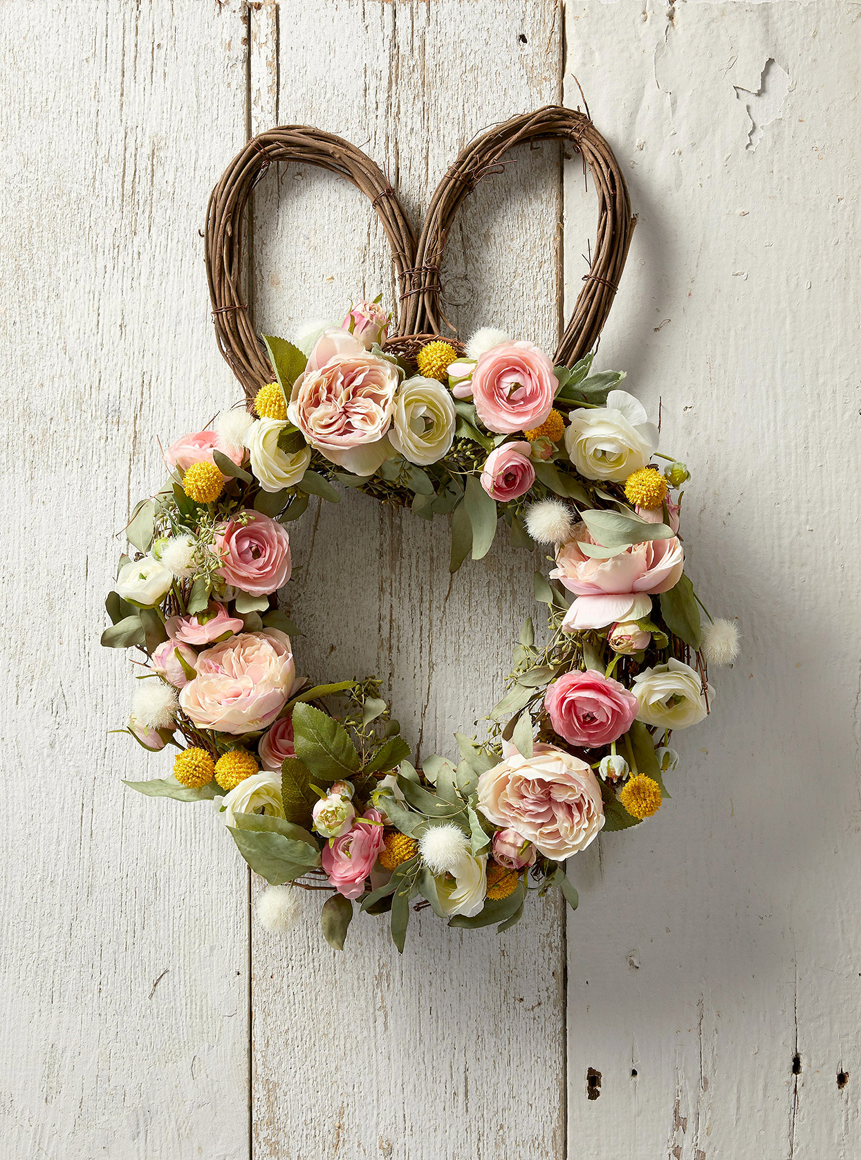 bunny-ears grapevine wreath with pink, white and yellow blooms