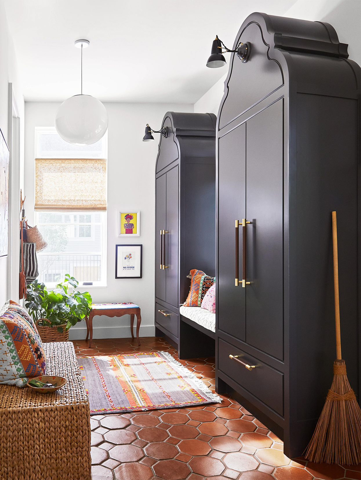 black twin storage armoires and terra-cotta floor tiles in mudroom