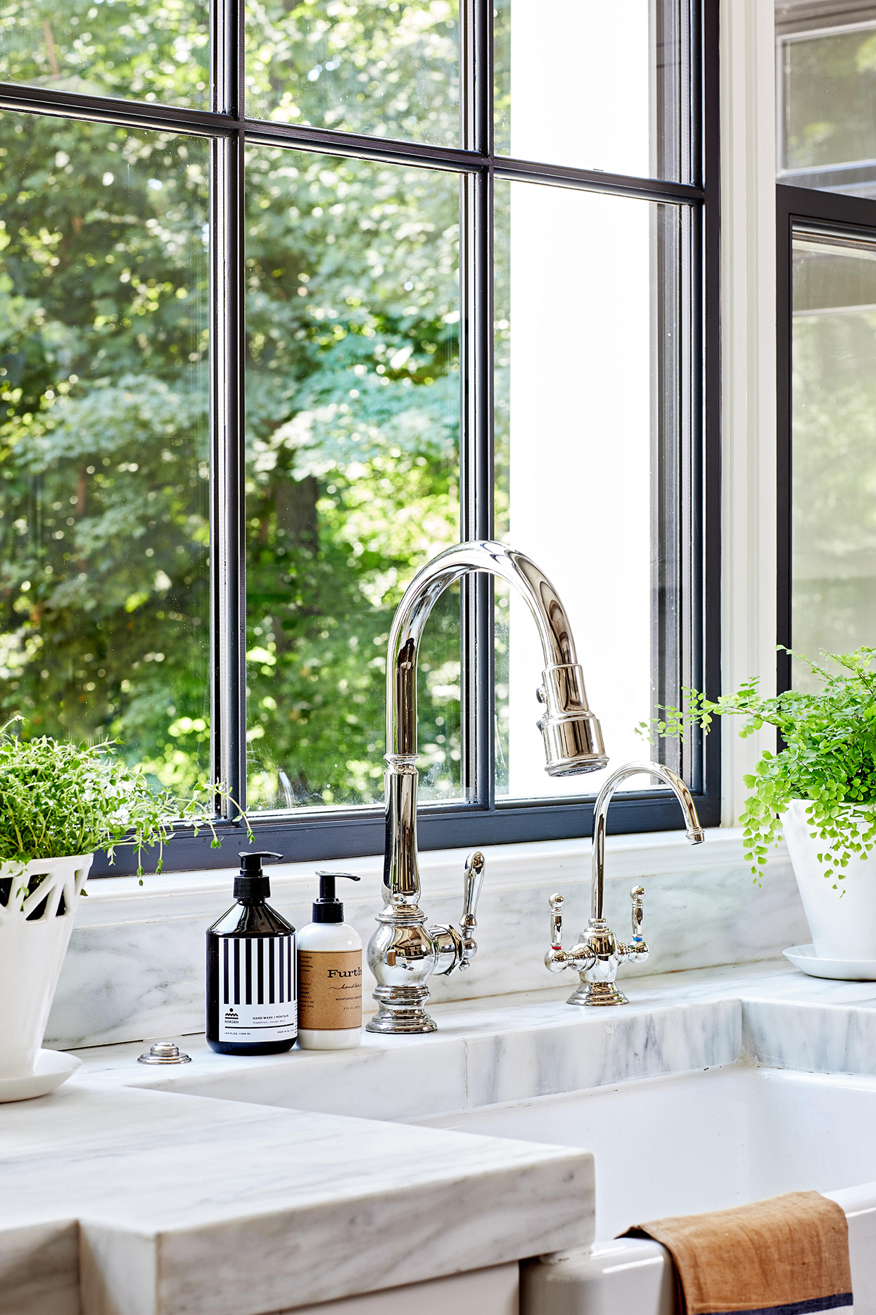chrome faucet on marble countertop with farmhouse sink