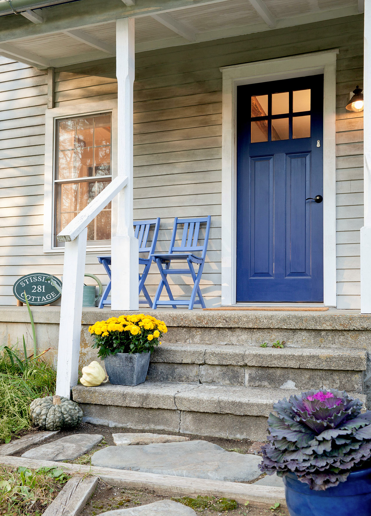 cinderblock patio with stairs up to blue door