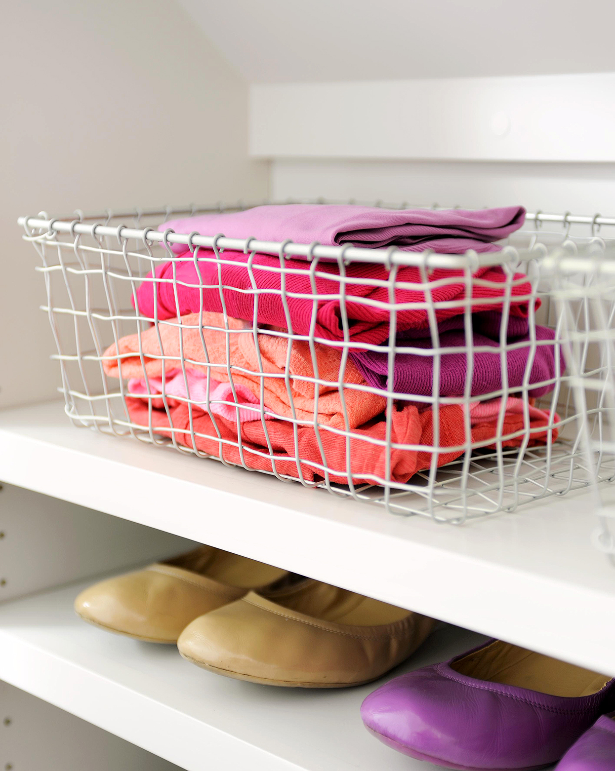 detail of clothes in wire basket sitting on closet shelf