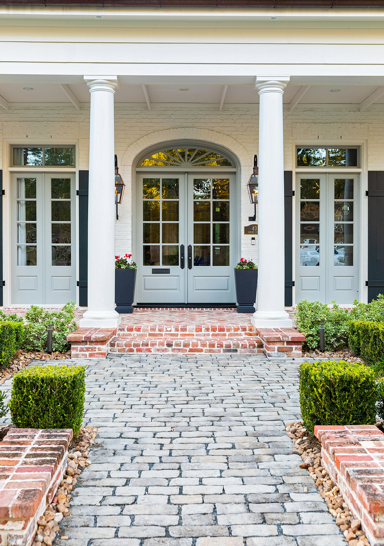 pale blue front doors of white colonial exterior with stone pathway
