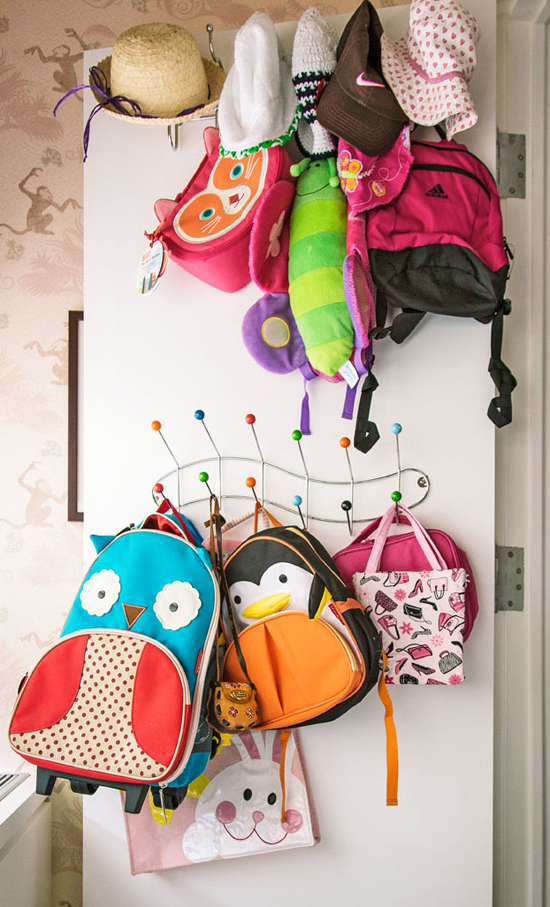 colorful children's backpacks and hats hanging on door