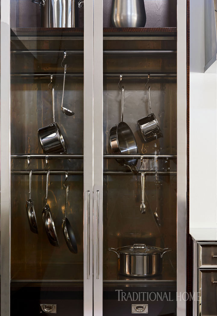 custom kitchen cabinets with glass doors and pots hanging inside