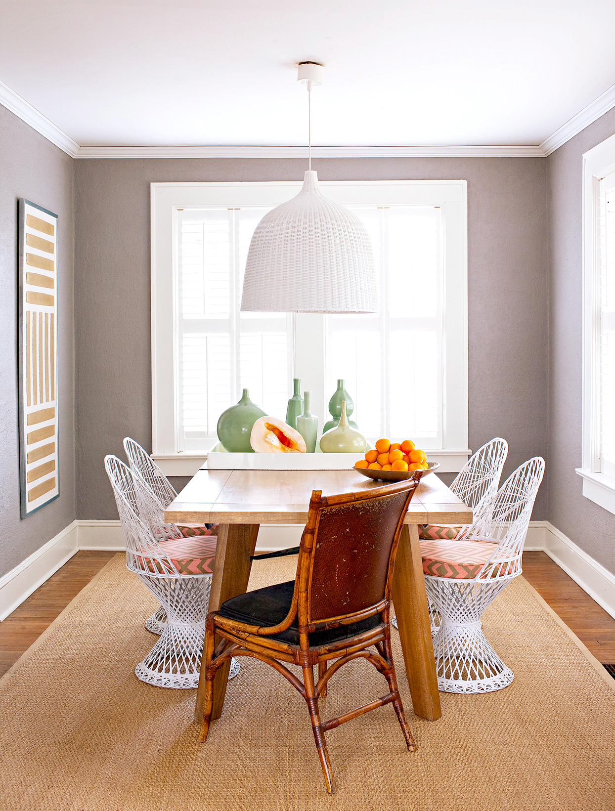 Dining area with gray walls and wicker chairs