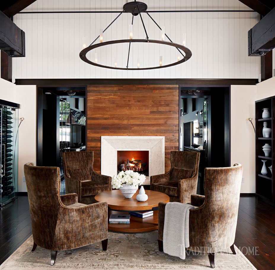 foyer with large pendant light, upholstered wing chairs and fireplace