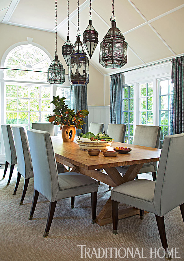high ceiling dining room with wooden table and ornate hanging lights