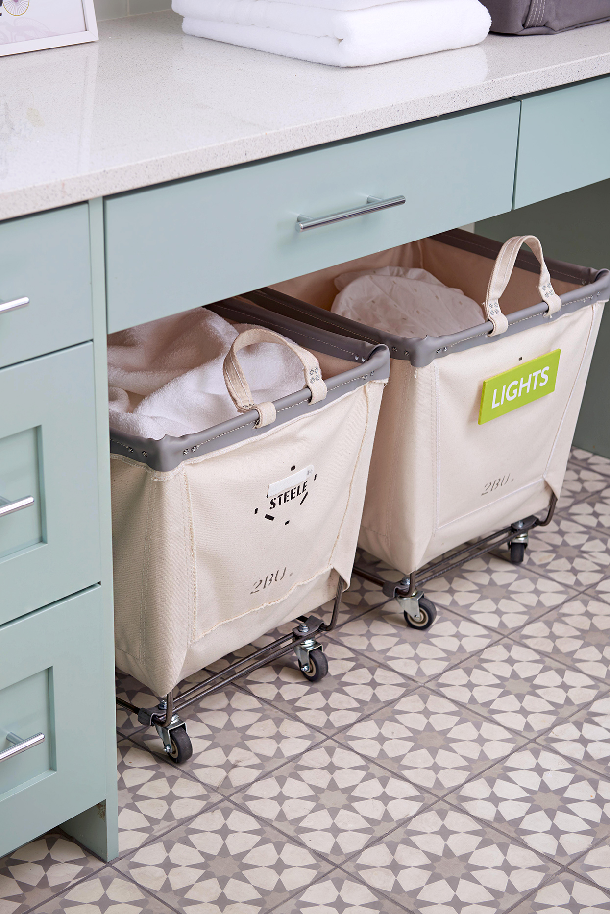 labeled bins with rollers underneath laundry room counter