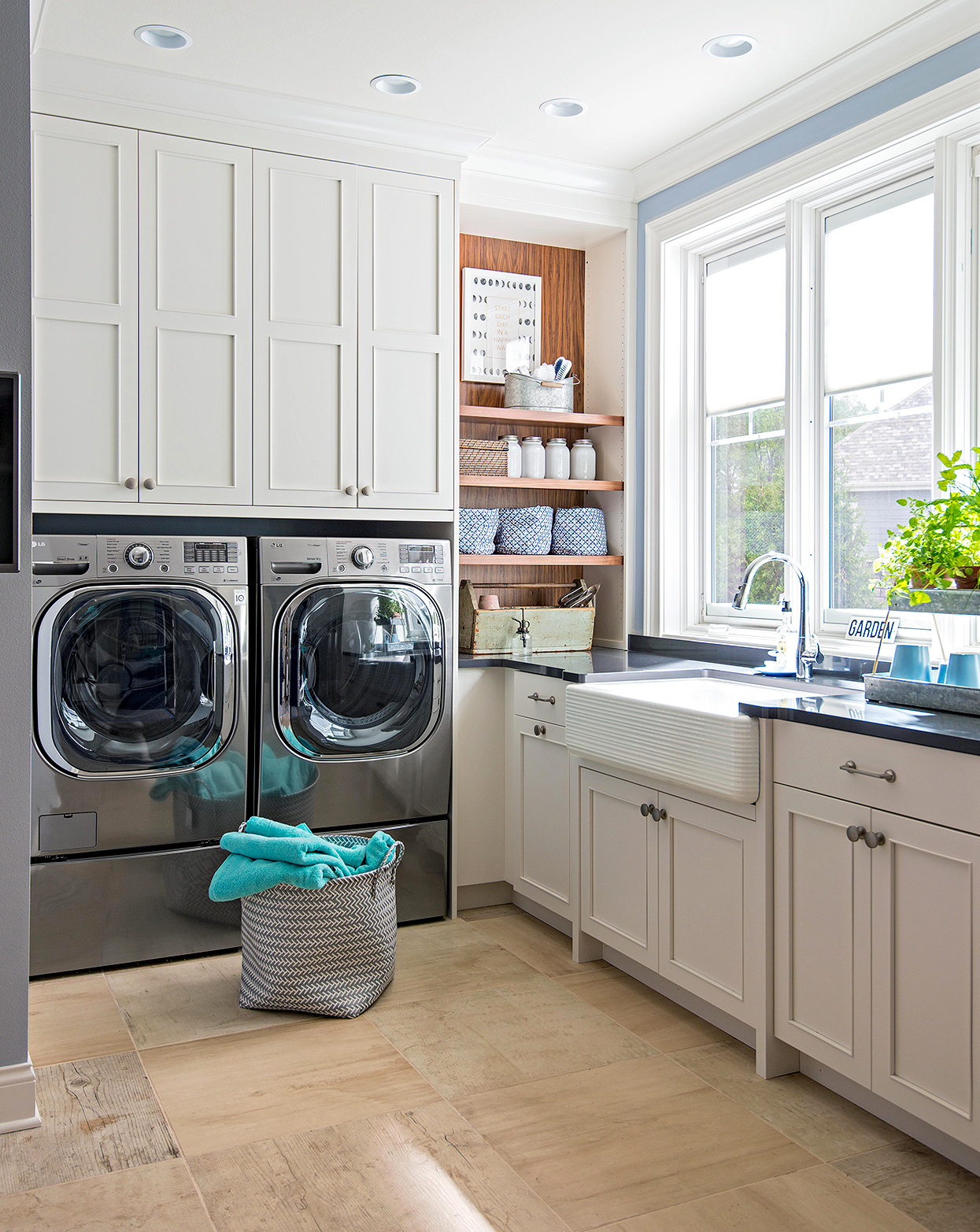 modern laundry room with bult-in shelving and farmhouse sink