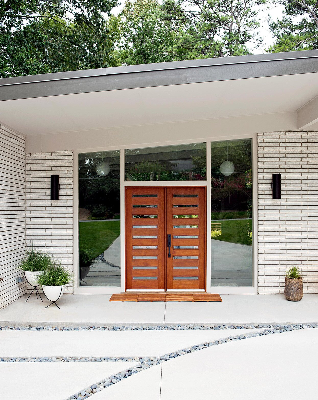 painted brick exterior of midcentury-modern home with wood front doors
