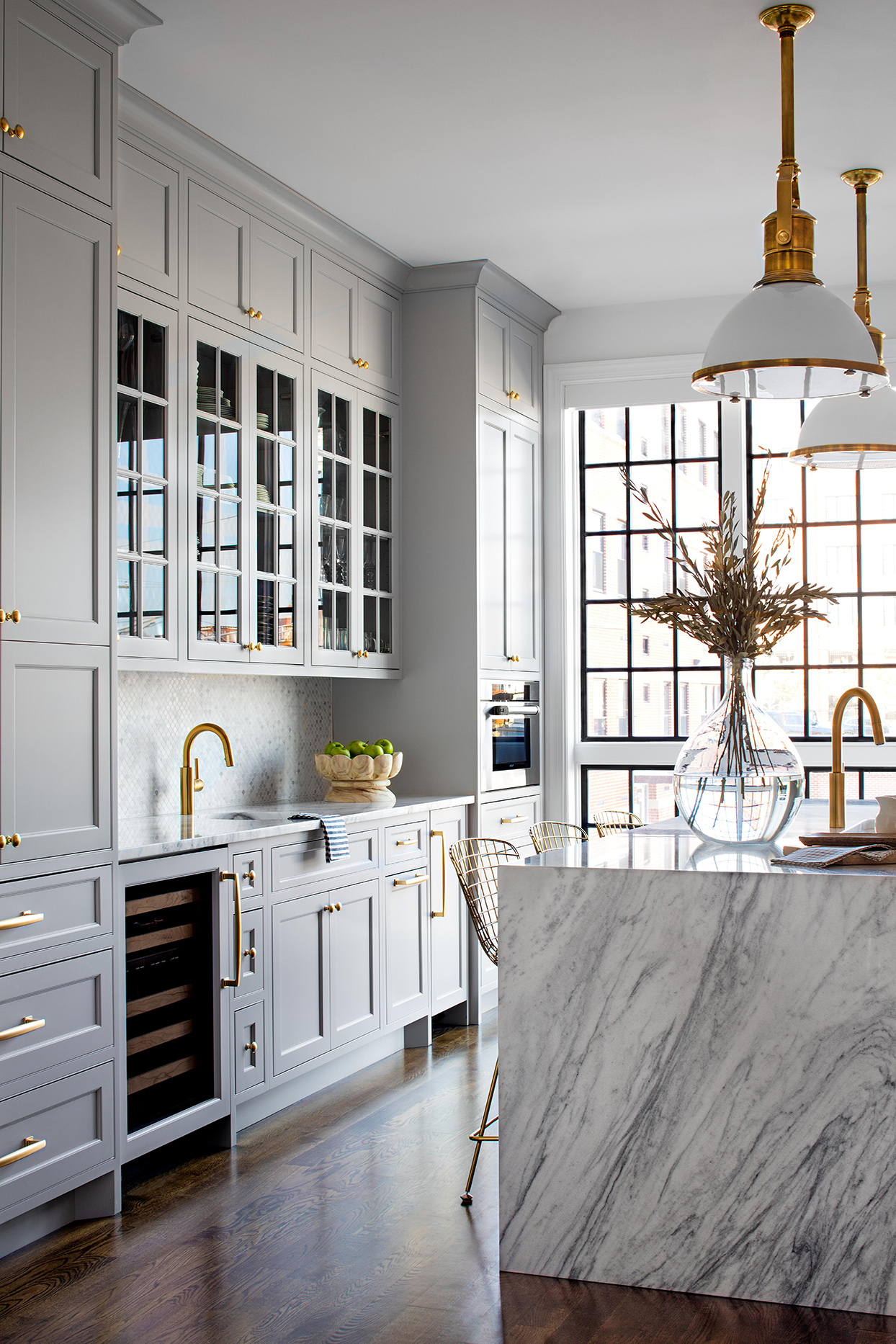 natural light flooding pastel gray kitchen with gold accents
