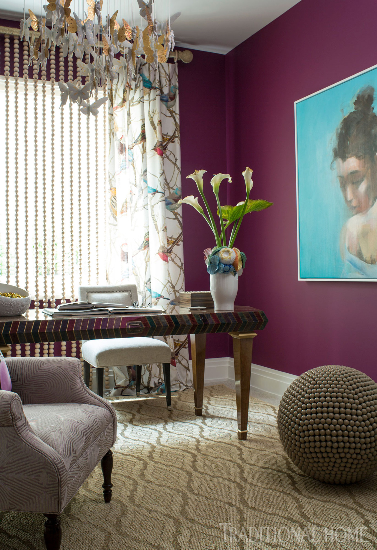 purple walls and jewel tone desk with chandelier