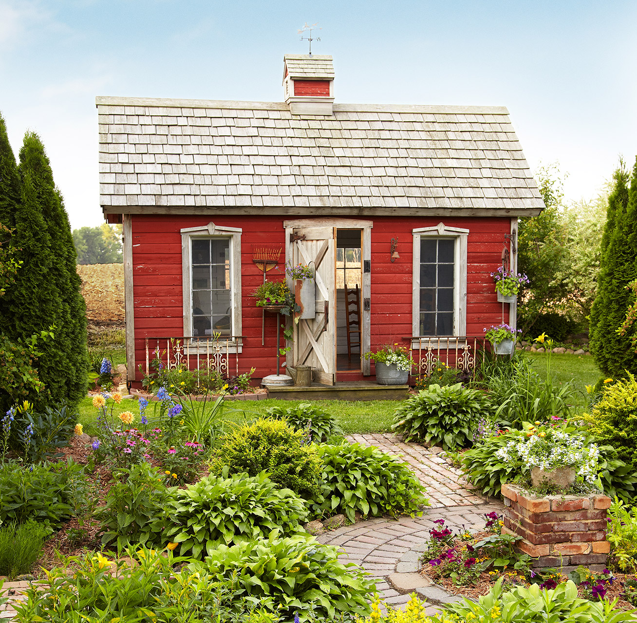 red garden shed with shake roof and weathervane