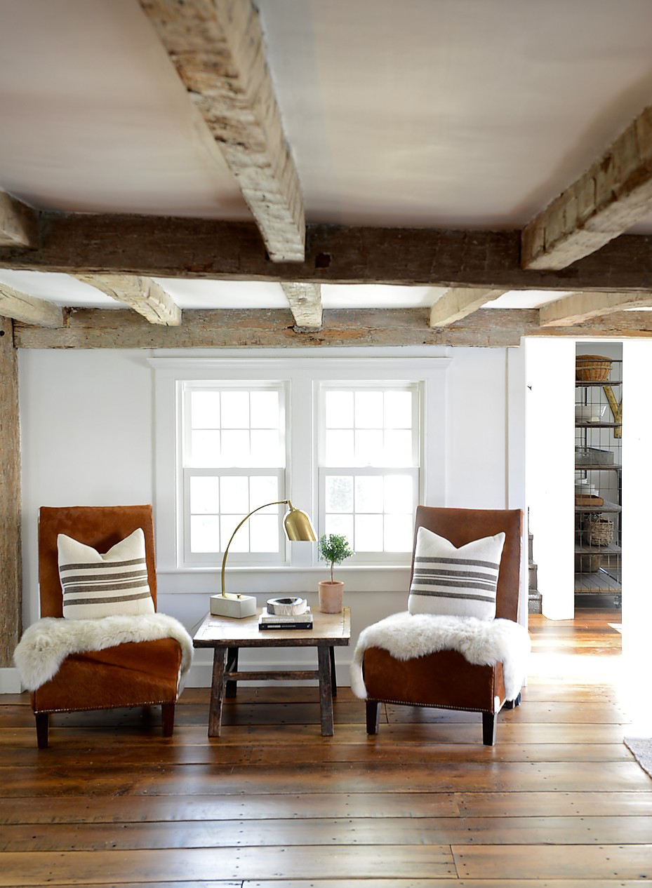 brown chairs with white furs and end table in neutral tones saltbox house