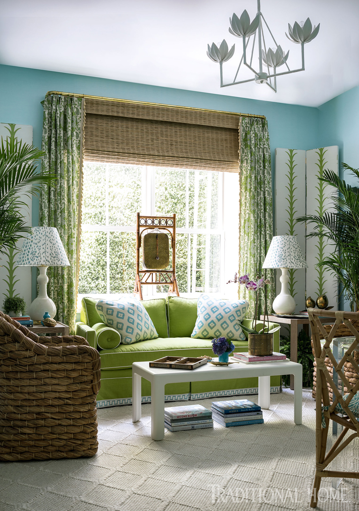 Seating area with green couch and patterned curtains