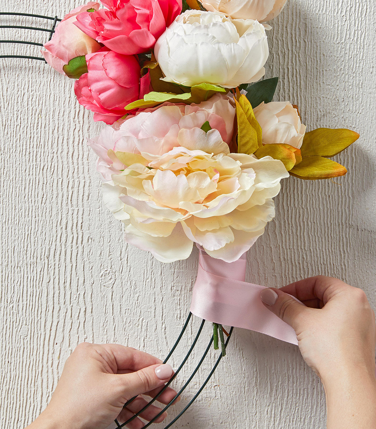 securing artificial floral stems to wreath with pink ribbon