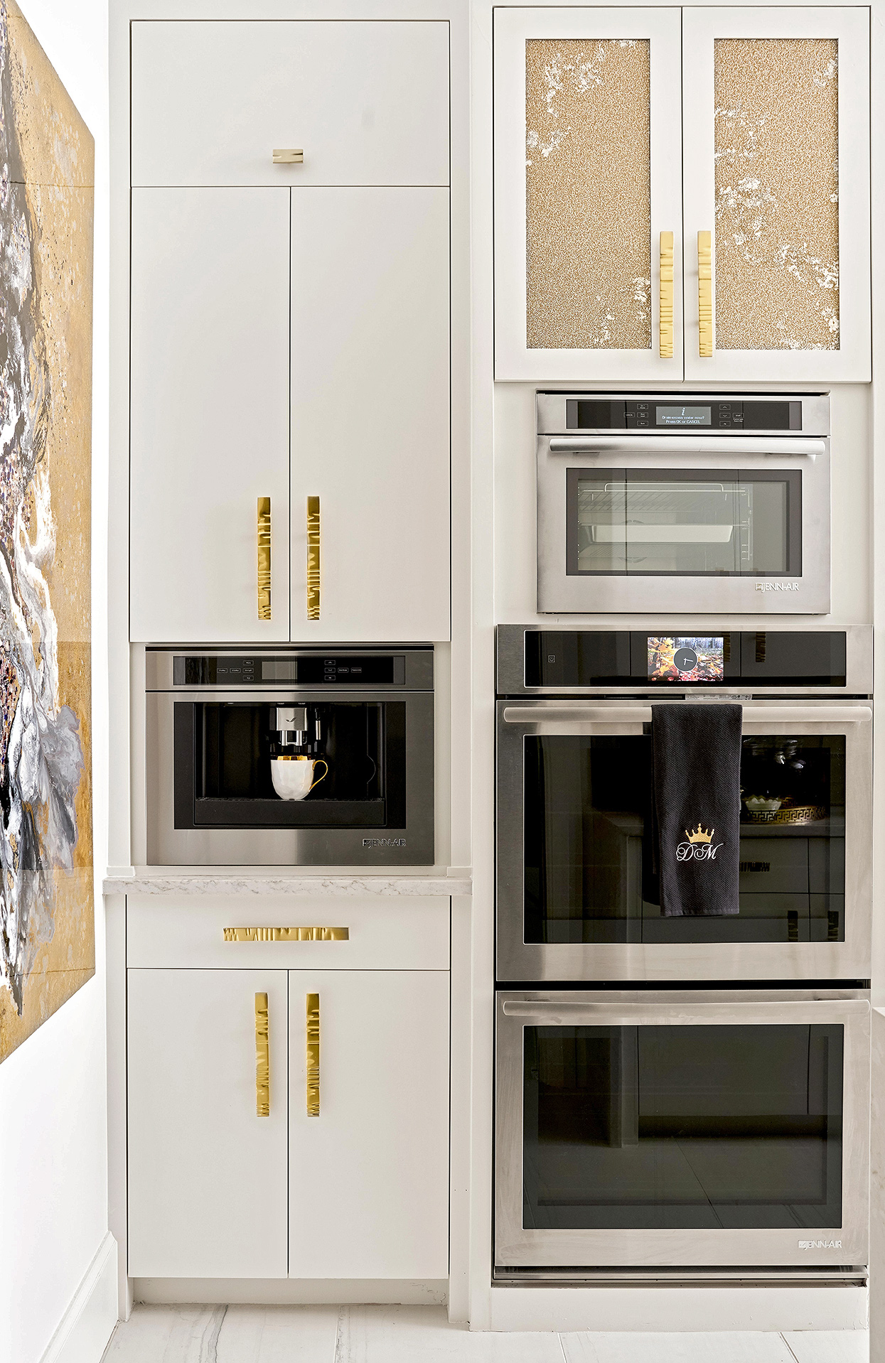 sleek white kitchen with modern appliances and gold details