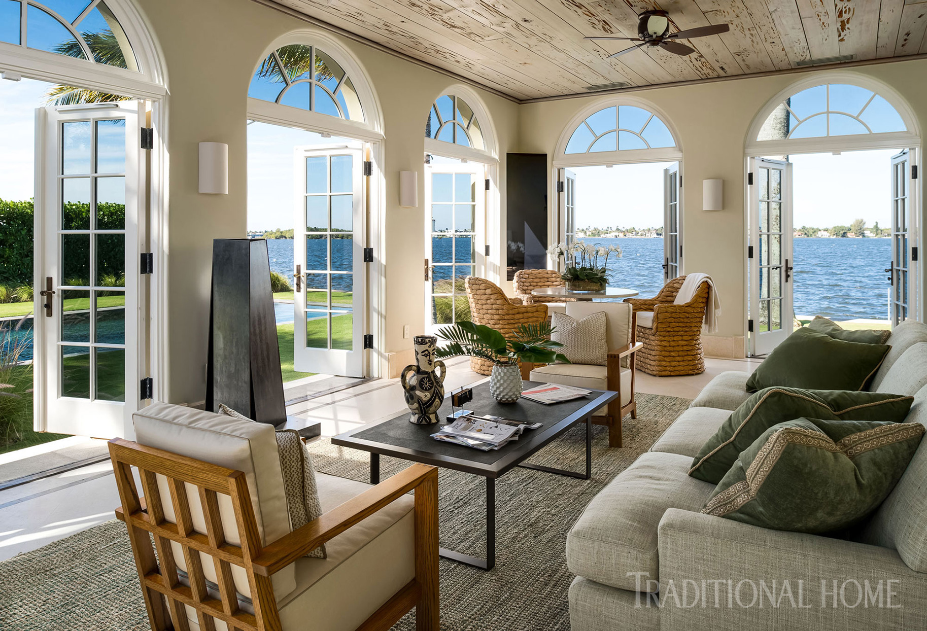 sunroom with arched doors opening to water