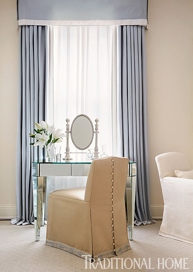 tall blue curtains above vanity and pearl trimmed chair
