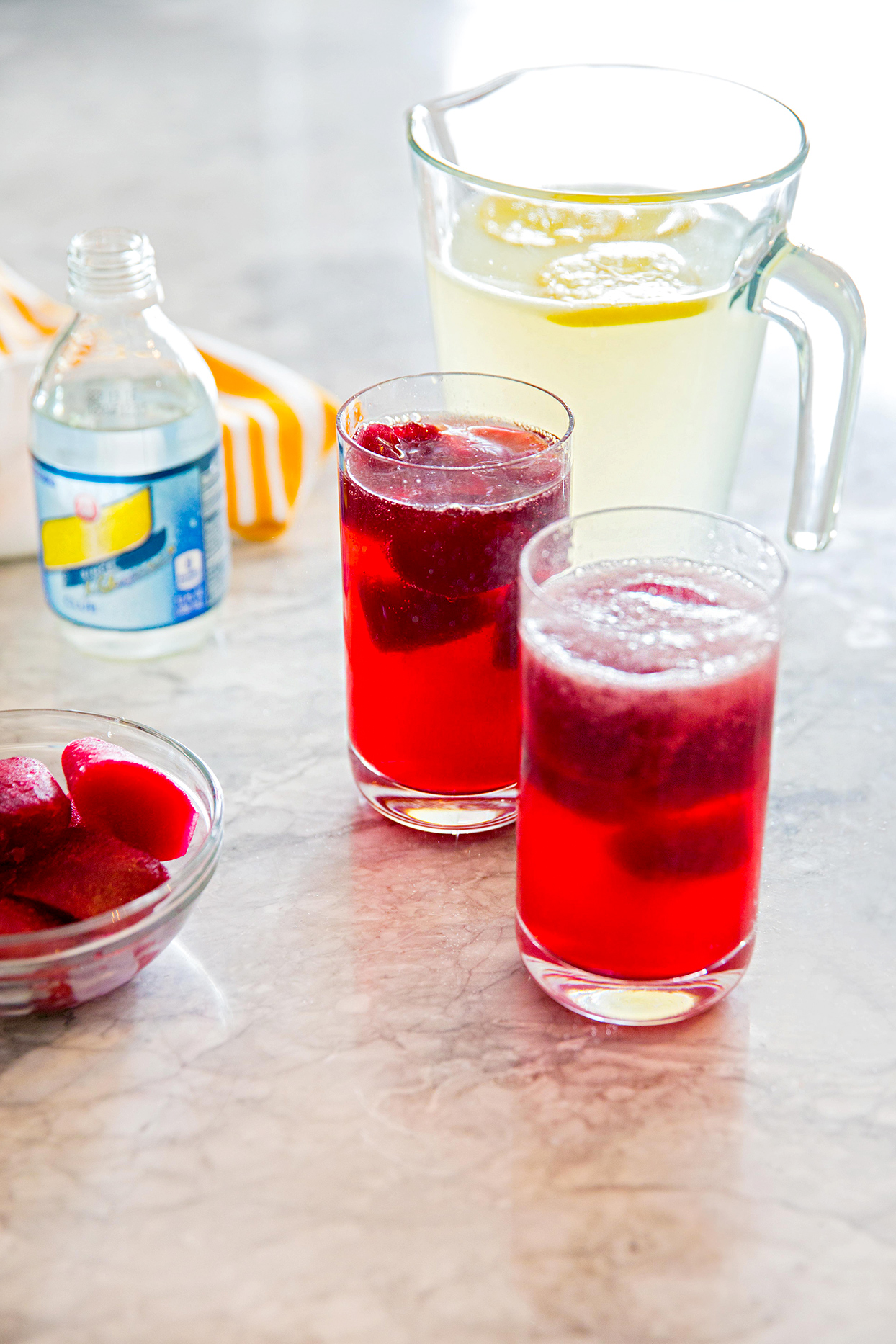 Two glasses and pitcher filled with beverages