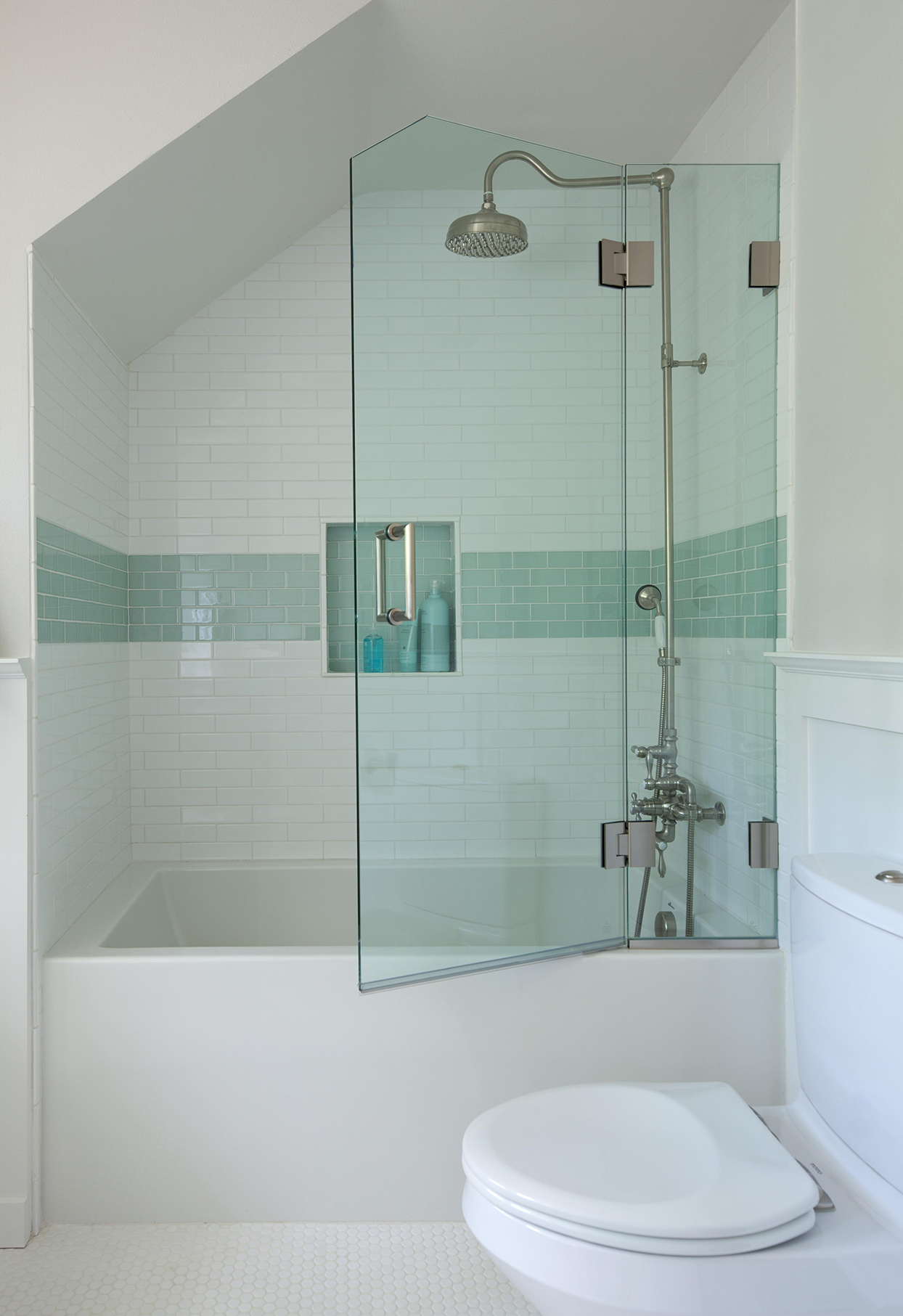 white bathroom with tiled shower and angled glass door