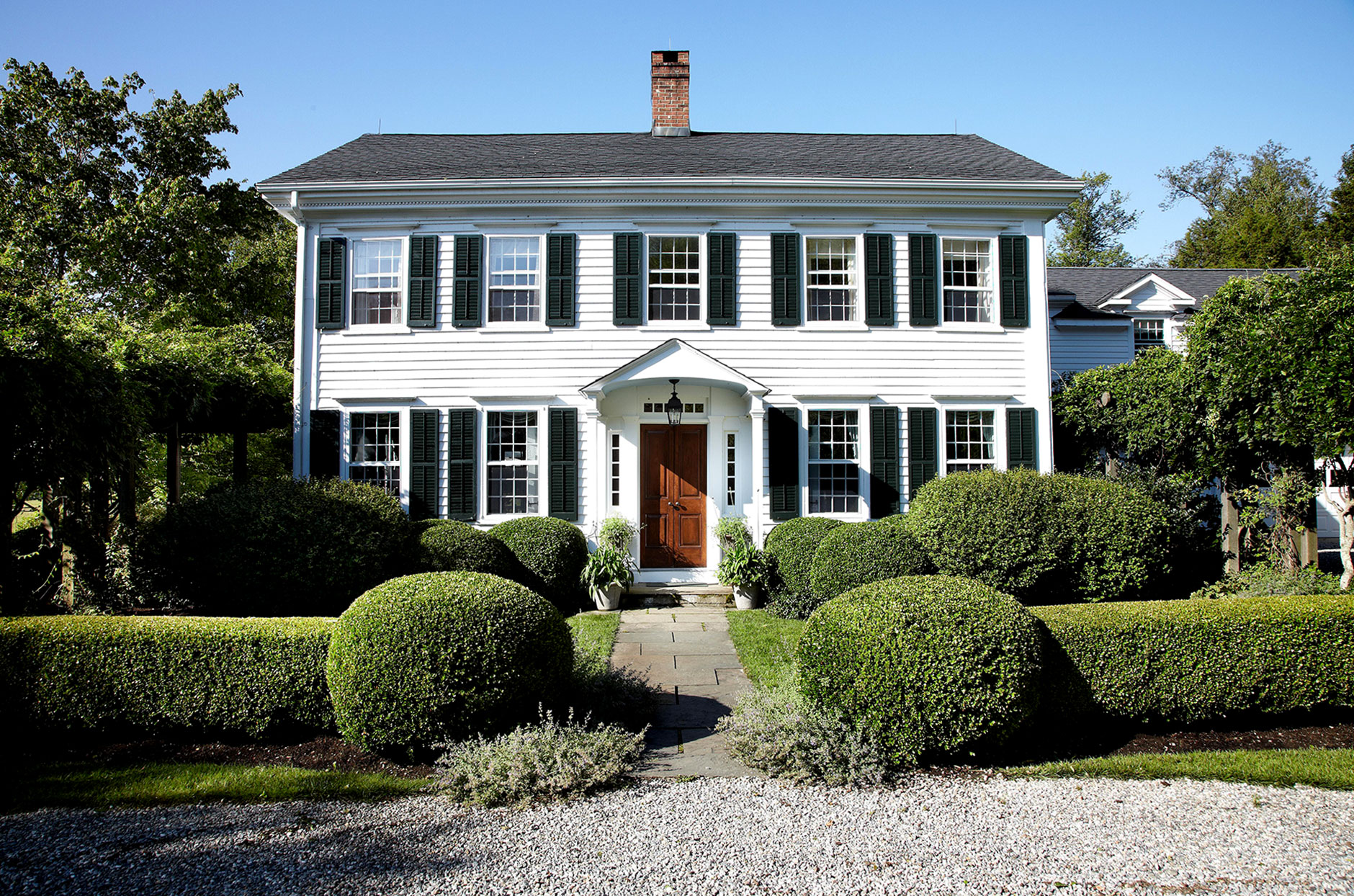 White colonial home with greenery in entryway