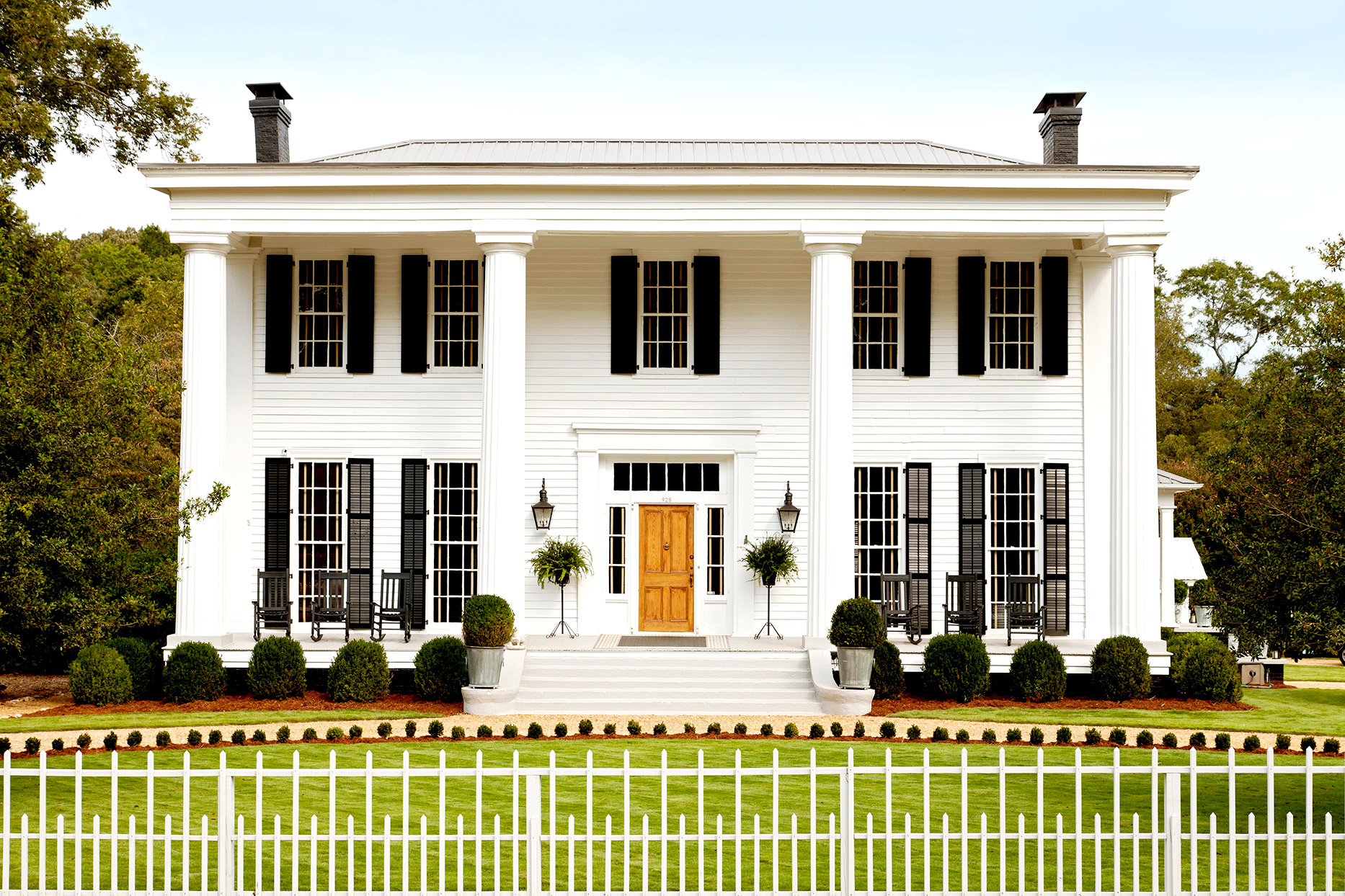 White colonial home with large columns and steps