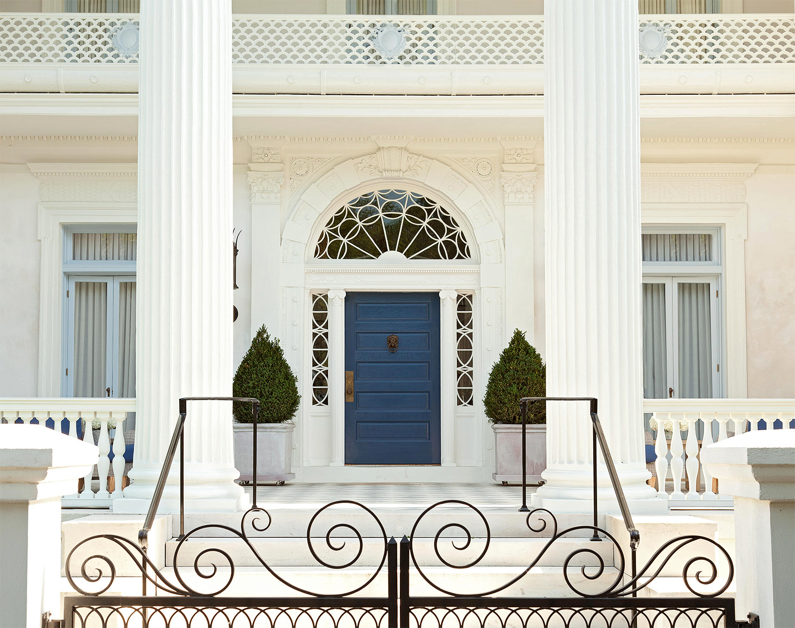 white exterior with columns and blue front door