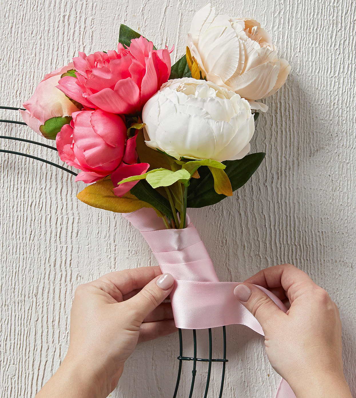 wrapping pink ribbon around artificial floral stems on wreath