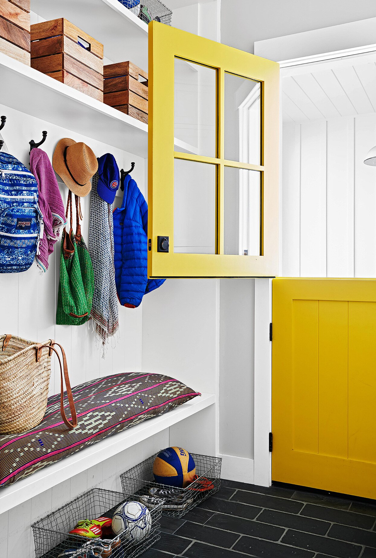 bold yellow dutch door in entryway with boho cushion