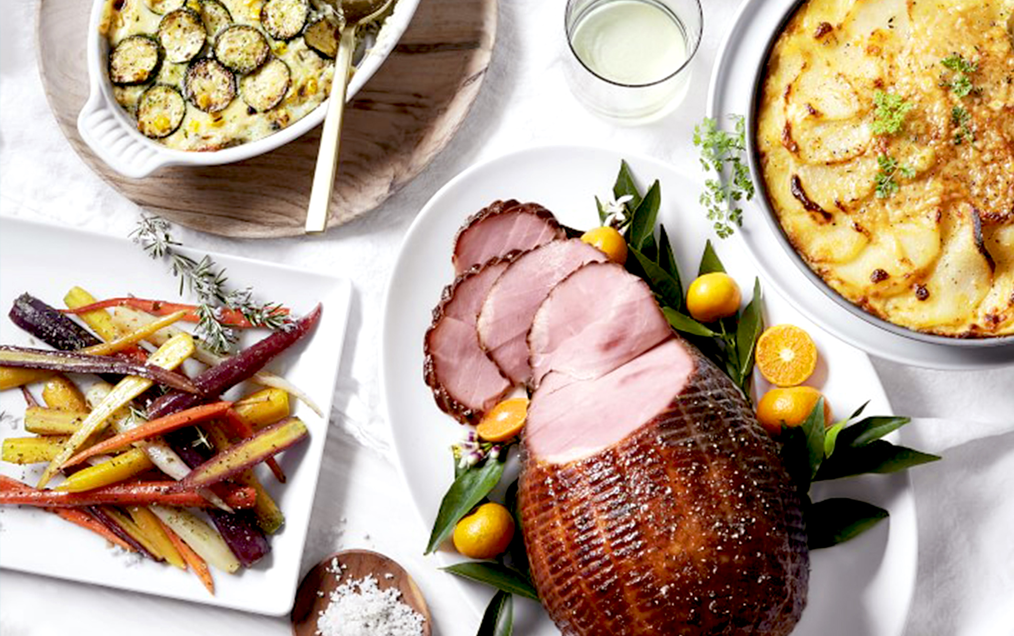 Overhead view of a Williams Sonoma Easter dinner with ham and side dishes