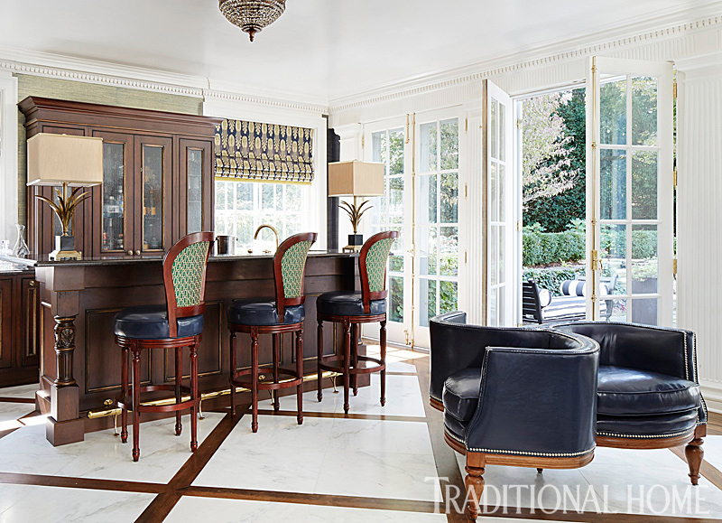 dark wood bar in room with marble floors and french doors